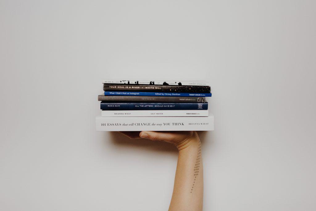 Hand mit Stapel von Büchern